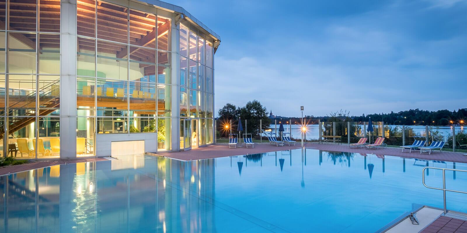 Großzügige Badelandschaft mit beheiztem Außenschwimmbecken und Seeblick
